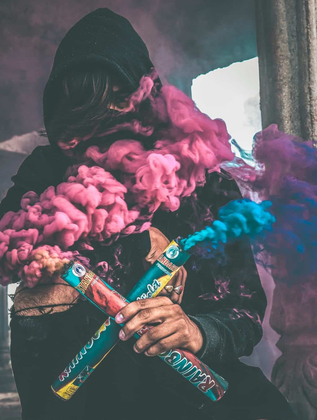 A Boy in Hood With Colorful Smoke